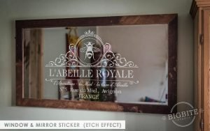 A mirror with the Royal Beekeeper Window Sticker, semi-transparent etch effect.
