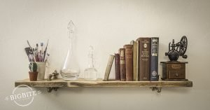 Rustic shelf attached to a wawll supports sets of antique books and two elegant flasks, the shelf is supported by brass and copper brackets.