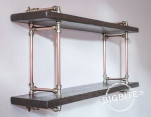 Emty bookshelf attached to the wall wth polished copper pipes and shiny brass joints