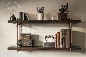 Insustrial bookshelf with decorative objects on it as antique books, old iron, and fancy small boxes.