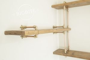 Copper pipe and brass steampunk corner bookshelf on the wall