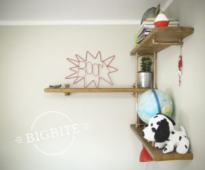 Copper and brass bookshelf in kid's room with toys displayed: a viking hat, a globe and a stuffed puppy