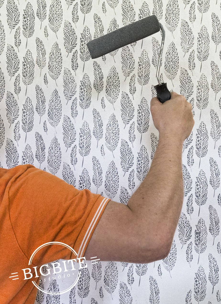 A man's hand with a paint roller on the background of wall with grey stenciled pattern