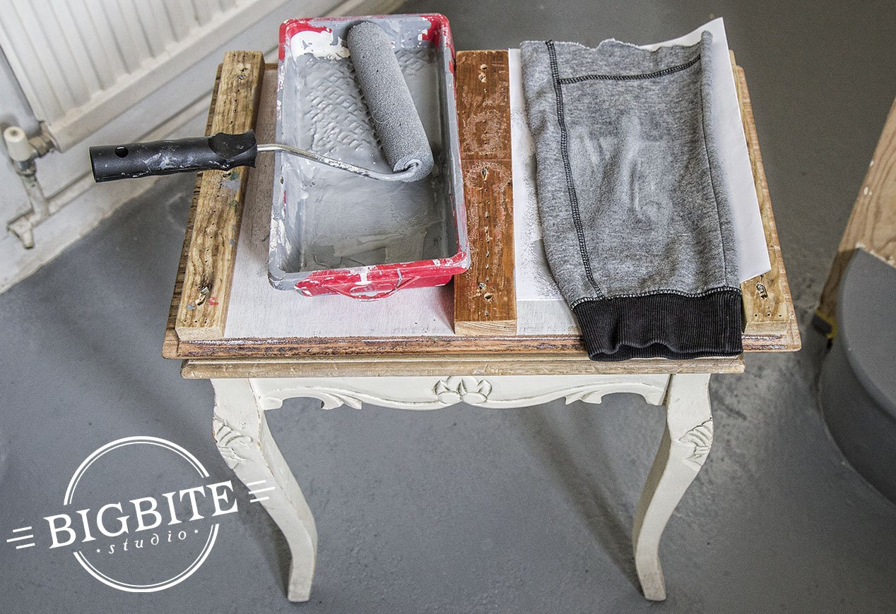 Picture shows a paint roler and tray laying on shabby chic coffee table