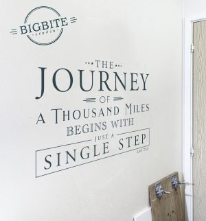 """Motivational Quote """"the journey of a thousand miles begins with juast a single step"""" on the white wall in a small room"""